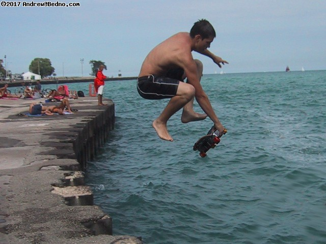 Extreme skateboarder jumping into lake.