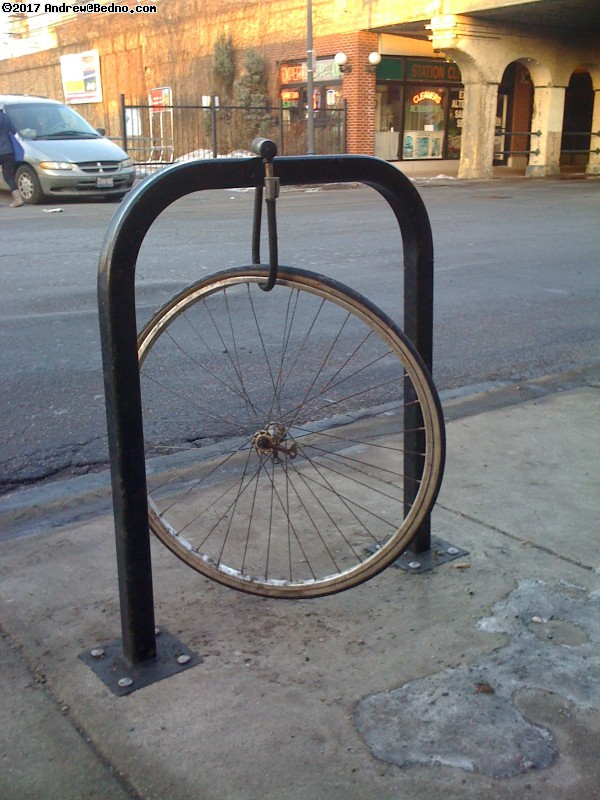 Lone locked bike wheel. (click for next photo)