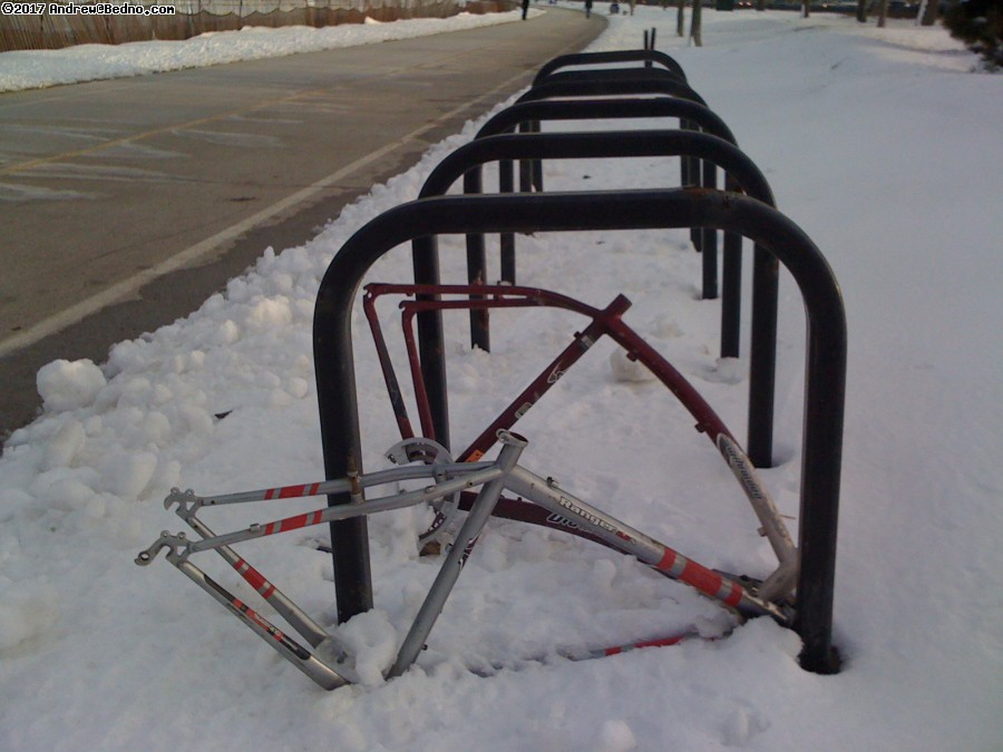 Lonely locked bike frames in snow.